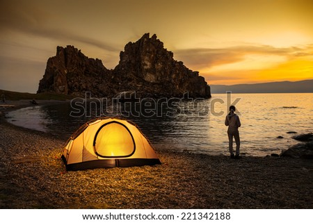 Tourist stand near tent and lake shore and looking at the beautiful sunset - stock photo