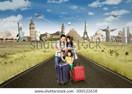 Tourist standing on the road with luggage and use digital tablet to see the famous place. Shot with famous landmarks on the back - stock photo