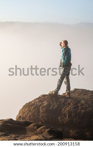 Tourist standing on the sandstone rock in national park Saxon Switzerland and watching over the misty and foggy morning valley.