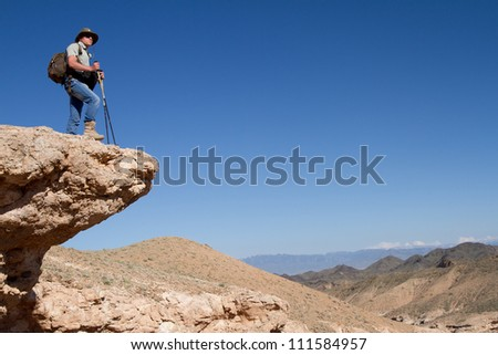 Tourist stands on the brink of a rock and looks in a distance