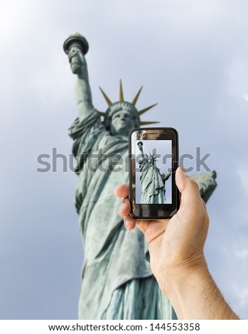 tourist takes a picture with his mobile of statue of liberty in new york - stock photo