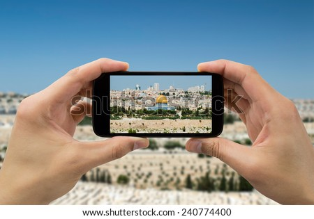 tourist takes a picture with his mobile of the Jerusalem old city  - stock photo