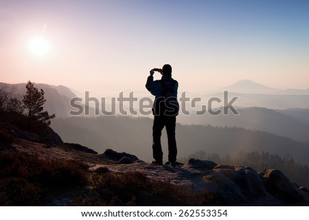 Tourist takes photos with smart phone on peak of rock. Dreamy fogy landscape, spring orange pink misty sunrise in a beautiful valley below rocky mountains. - stock photo