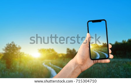 Tourist taking a photo of nature using a smartphone, point of view shot