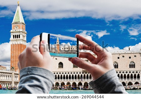 Tourist taking a picture of Campanile and Ducale or Doge Palace in Venice, Italy - stock photo