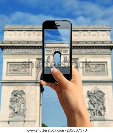 Tourist taking a picture with mobile phone of Arc de Triomphe - stock photo