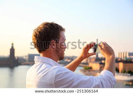 Tourist taking photograph of sunset in Stockholm skyline and Gamla Stan. Man photographer taking photos using smartphone camera. Male traveler sightseeing visiting landmarks in Sweden, Scandinavia. - stock photo