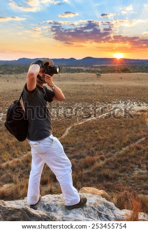 Tourist taking photos at sunset near the famous rock formation 'La Fenetre' in Isalo, Madagascar - stock photo