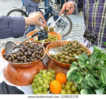 Tourist tastes artisan olives on village market - stock photo