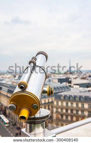 Tourist telescope over Paris landscape on Lafayette Gallery terrace - stock photo
