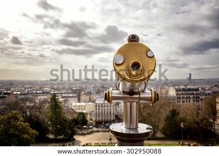 Tourist telescope positioned above the city of Paris. The view is from The Sacre Coeur in Montmartre - stock photo