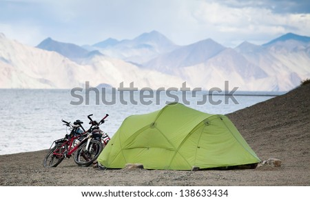 tourist tent and bikes near the blue lake, among the high peaks of the Himalayas - stock photo