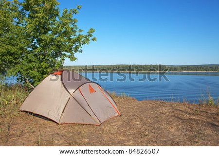 Tourist tent by the river - stock photo