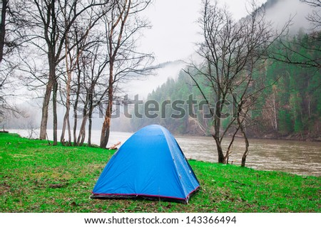Tourist tent in forest camp among meadow on river on the mountain background in smoke - stock photo