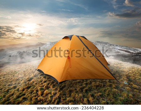 Tourist tent in mountains in the autumn - stock photo