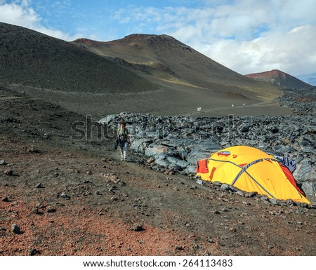 Tourist tent stands next to active lava flow from a new crater on the slopes of volcanoes Tolbachic, on background volcano Bolshaya Udina - Kamchatka, Russian Federation