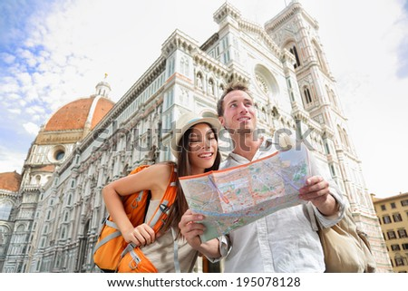 Tourist travel couple by Florence cathedral, Italy looking at map in front of Il Duomo di Firenze also called Basilica di Santa Maria del Fiore. Main tourist attraction and landmark in Florence, Italy - stock photo