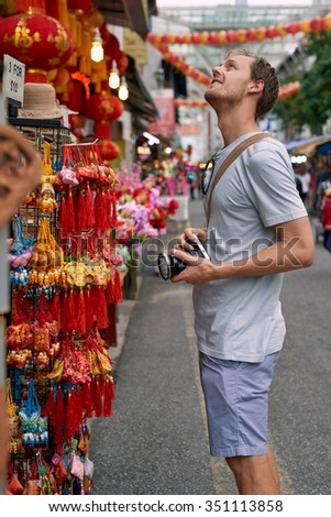 Tourist traveler with camera in asian city chinatown exploring cultural attractions and shopping for souvenir trinkets - stock photo