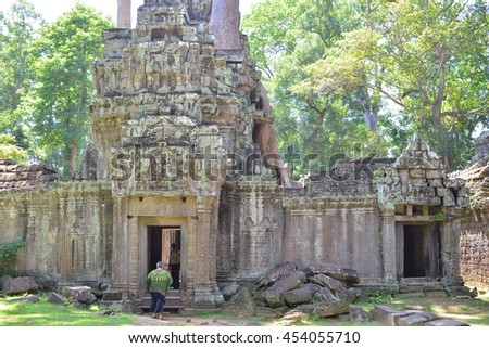 Tourist walking into Ta Prohm Temple, surrounded by nature.