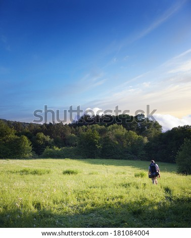 tourist walking on a footpath across the field - stock photo