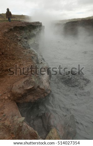 Tourist walks near edge of an active steamy volcanic pool bubbling away, near the Hveragerdi Hot Spring River Trail in Reykjadalur, Iceland.