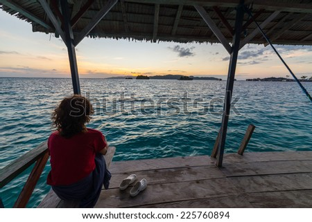 Tourist watching a relaxing sunrise in the remote Togean Islands, Central Sulawesi, Indonesia. - stock photo