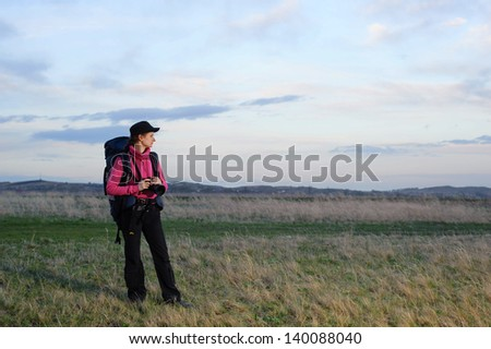 tourist with a backpack and a camera on the background of sky