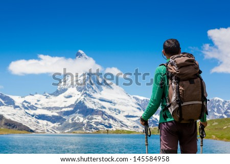 Tourist with a backpack and mountain panorama. Matterhorn. Swiss Alps - stock photo