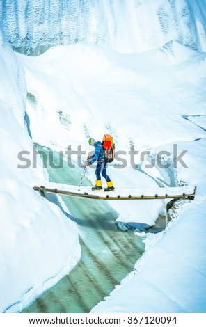 Tourist with a backpack goes via glacier - stock photo