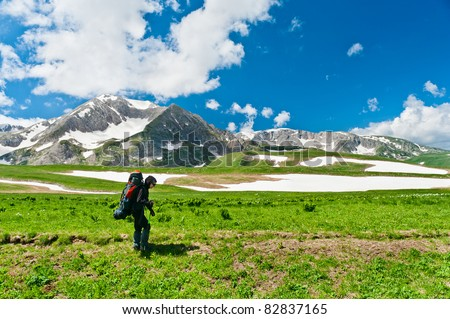 tourist with a backpack on the background of snowy mountains - stock photo