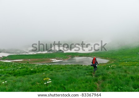 tourist with a backpack walking along the road in the mountains - stock photo