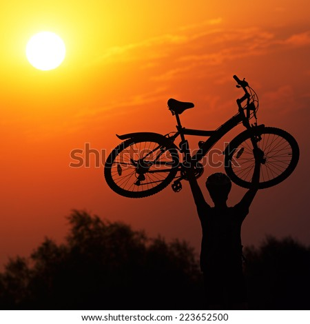 Tourist with a bike on the sunset background. - stock photo