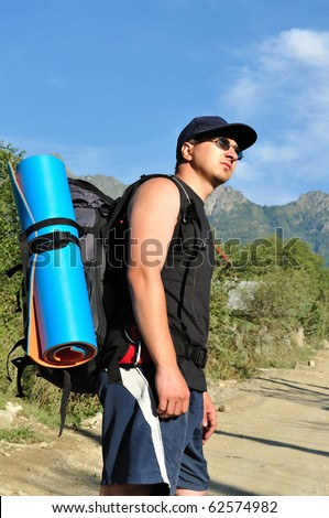 Tourist with a large backpack is a high mountain, on the road, photos in profile - stock photo