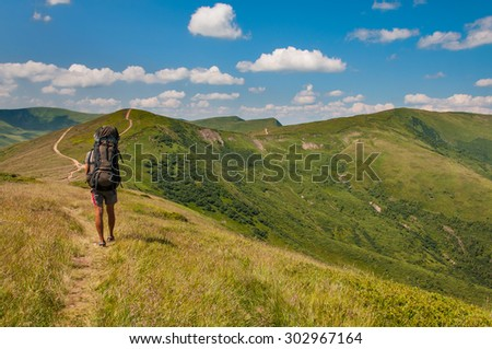 Tourist with a large backpack walking along the trail in the mountains - stock photo