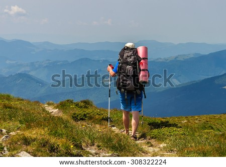 Tourist with a large backpack walking along the trail in the mountains