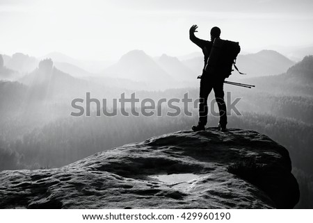 Tourist with backpack and poles in hand shadowing eyes. Sunny spring daybreak in rocky mountains. Hiker on rocky view point above misty valley. . Black and white photo - stock photo