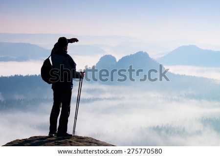 Tourist with backpack and poles in hand. Sunny spring daybreak in rocky mountains. Hiker with sporty backpack stand on rocky view point above misty valley.  - stock photo