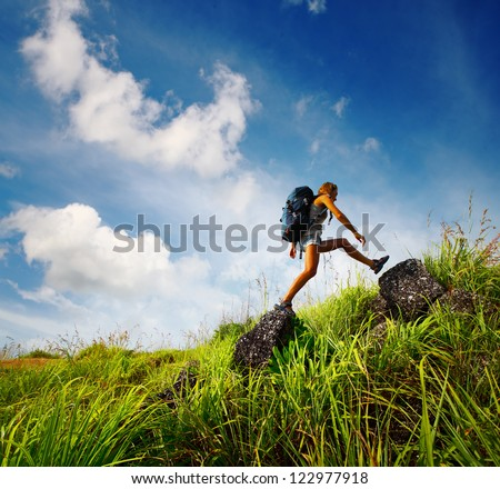 Tourist with backpack crossing rocky terrain with grass at sunny day