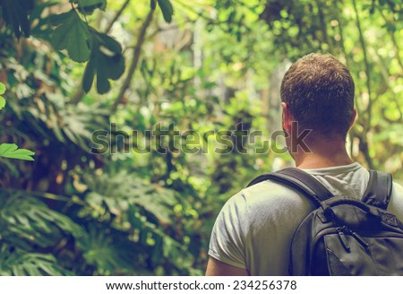 Tourist with backpack in the jungle. Vintage effect. Space for your text. - stock photo