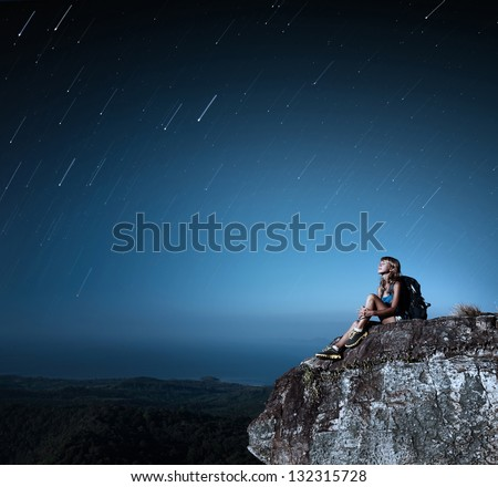 Tourist with backpack relaxing on top of a mountain at bright night with stars in a sky