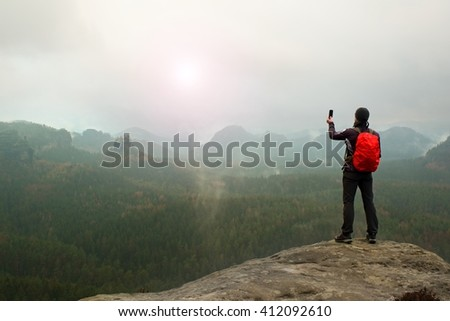 Tourist with backpack takes photos with smart phone of rainy vally. Melancholy atmosphere in foggy valley below - stock photo