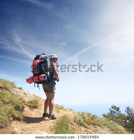 Tourist with baclpack on the mountain path at the background of blue sky