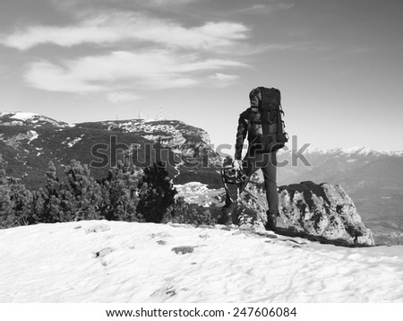 Tourist with big backpack and snowshoes standing on rocky view point and watching into misty rocky mountains. National park Alps park in Italy. Sunny winter morning. - stock photo