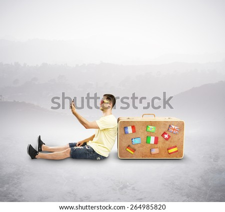 tourist with cellphone sitting near travel bag with flag - stock photo