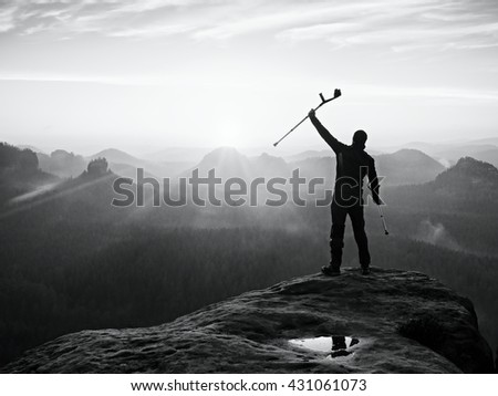 Tourist with forearm crutch above head achieved mountain peak. Hiker with broken leg in immobilizer and medicine  poles hold hand in air. Colorful misty valley bellow silhouette.Black and white photo