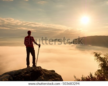 Tourist with hiking poles stand on cliff at heather bush on peak of rock empire. Man is watching over creamy fog in  valley bellow to big  Sun