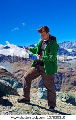 Tourist with map on mountains background. - stock photo