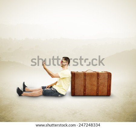 tourist with phone sitting near travel bag - stock photo