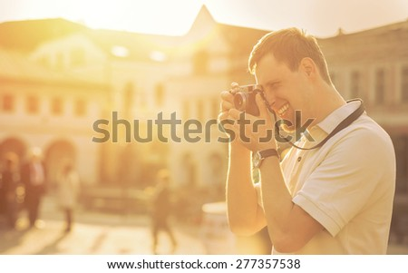 Tourist with photo camera shooting on the street under sunlight - stock photo
