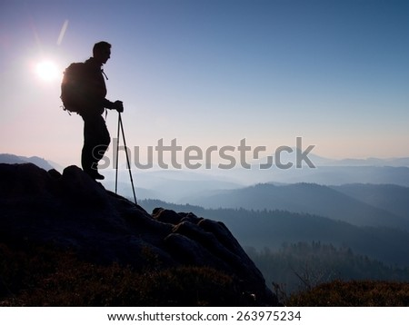 Tourist with sporty backpack and poles in hands stand on rocky view point and watching into deep misty valley bellow. Sunny spring daybreak in rocky mountains. - stock photo